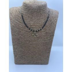 collar con cordoncito con bolitas y pieza de acero dorado con los puntos cardinales